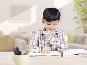 10 year-old asian elementary schoolboy doing homework at home.