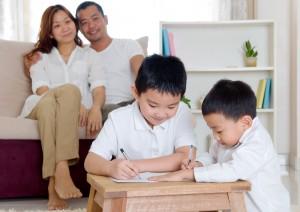 Asian parent looking at their kids doing homework
