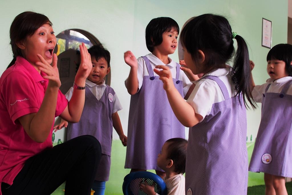 preschool teacher singing with children